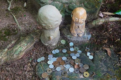 Jizo sama statuettes next to pile of Japanese coins